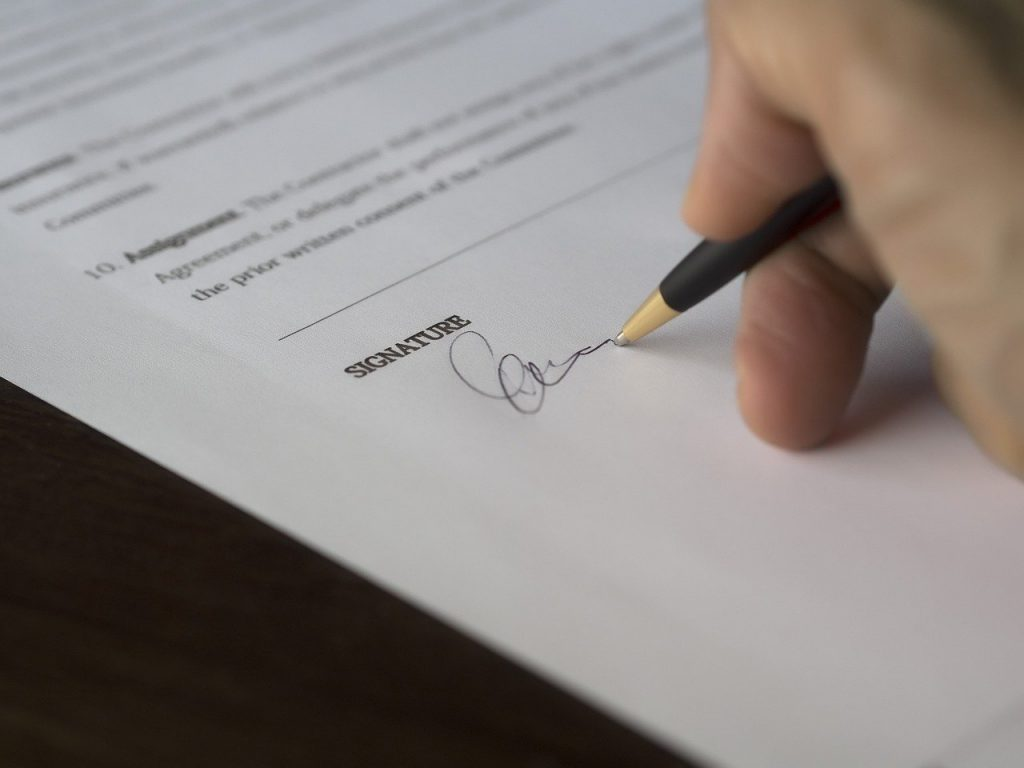 hand signing a contract to show the type of document that might benefit from proofreading and business services